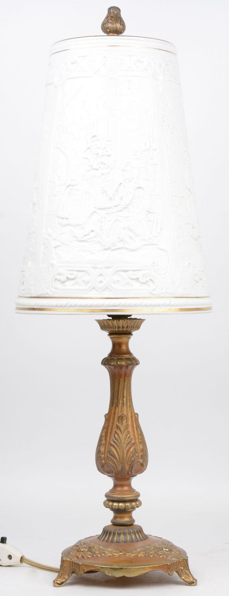 Een schemerlampje met messingen voet en met kapje van monochroom wit porselein, versierd met taferelen in reliëf.