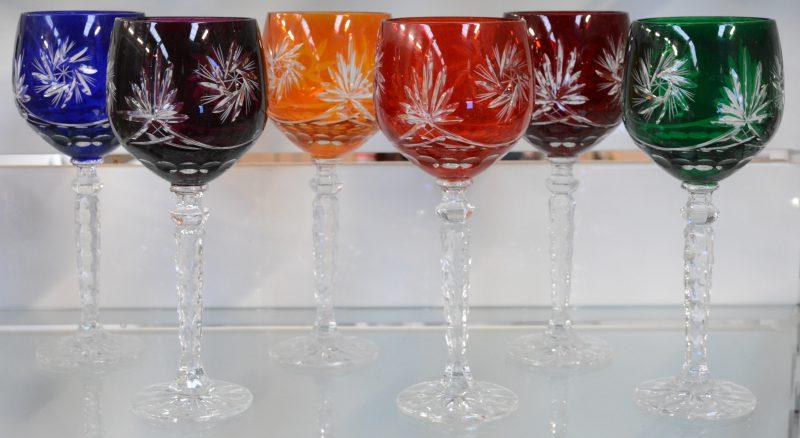 Een reeks van zes geslepen kristallen glazen met verschillend gekleurde kelken.