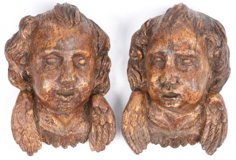Een paar gesculpteerd houten engelenkopjes met sporen van verguldsel.