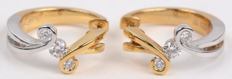 Een paar 18 karaats wit en geel gouden oorbellen bezet met briljanten met een gezamenlijk gewicht van +- 0,14 ct.