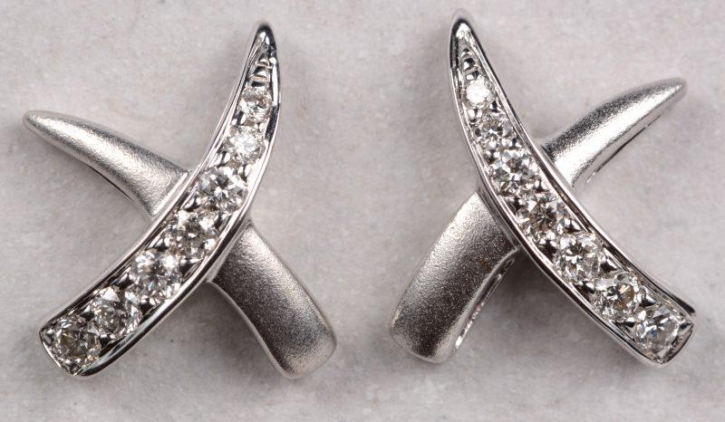 Een paar 18 karaats wit gouden oorbellen bezet met briljanten met een gezamenlijk gewicht van +- 0,18 ct.