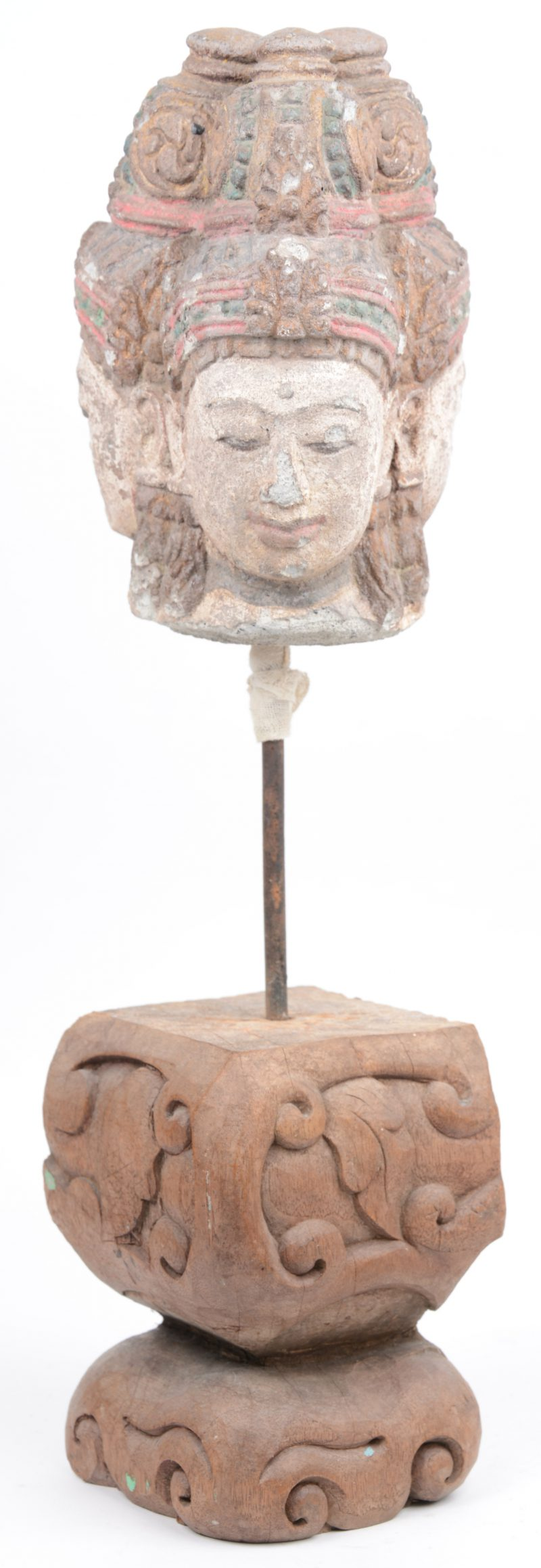 Een gepolychromeerd stenen Boeddhahoofd met drie gezichten. Op houten sokkel.