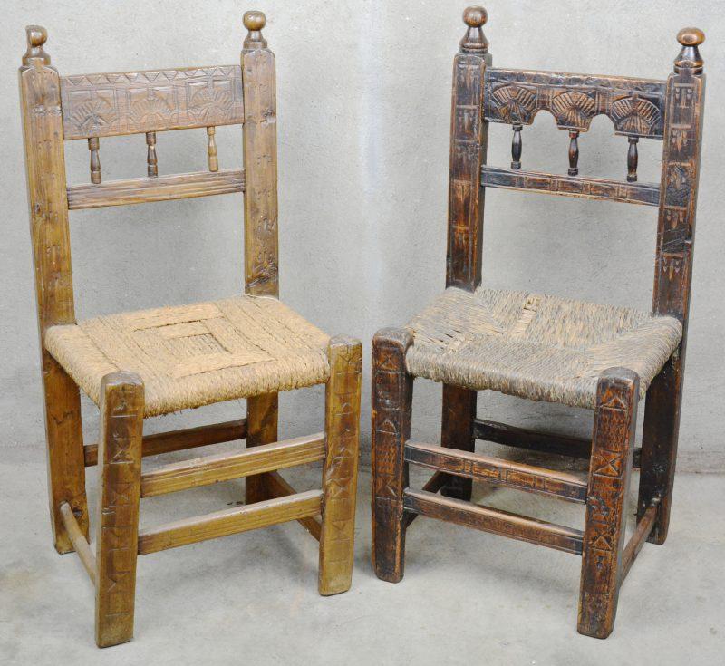 Twee grenenhouten haardstoeltjes met gesculpteerde rug en met rieten zit.