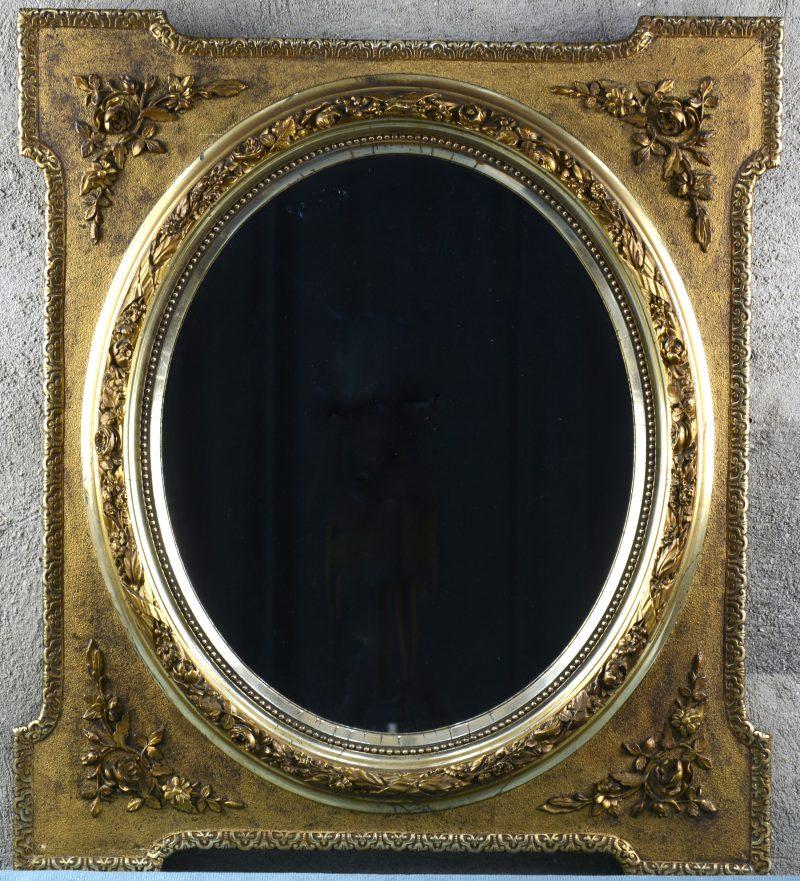 Een ovale spiegel in rechthoekige vergulde lijst, versierd met bloemenguirlandes.