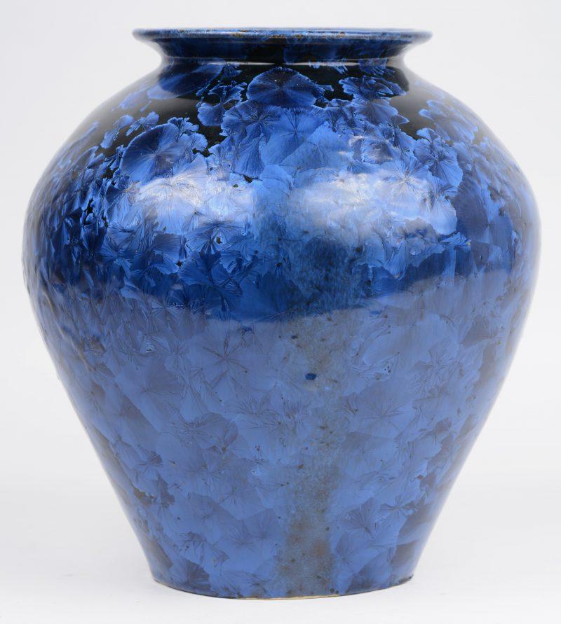 Een porseleinen vaas met blauw op zwart decor van zink, kobalt en titanium. Onderaan gesigneerd en gedateerd 1975.