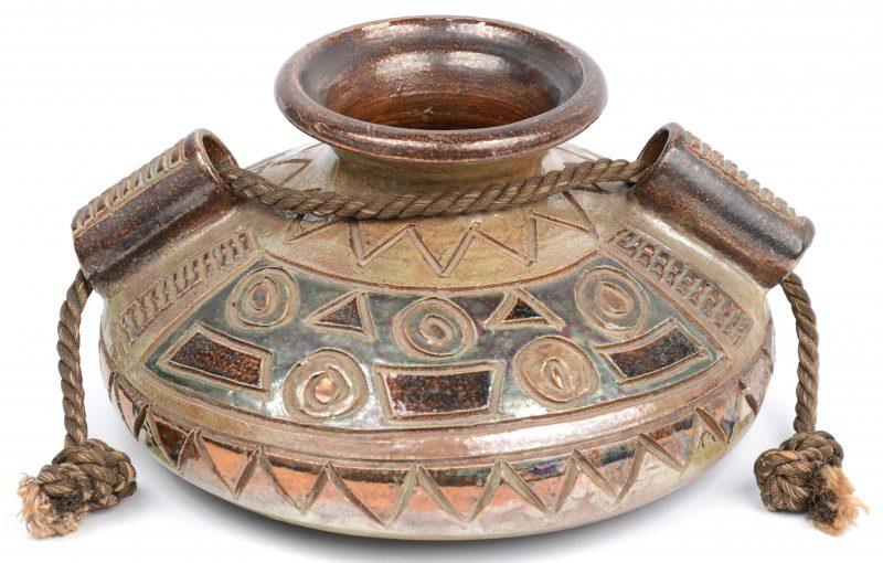 Een platte vaas van meerkleurig geglazuurd steengoed met reliëfdecor. Onderaan gemerkt.