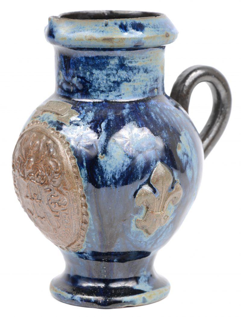 Een schenkkannetje van blauw geglazuurd steengoed met een wapenschild en twee Franse lelies in reliëf. Onderaan gemerkt. Kleine schilfer aan de rand.