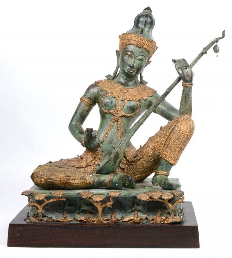 """""""Boeddhistisch figuur met sitar"""". Een bronzen beeld op houten sokkel."""