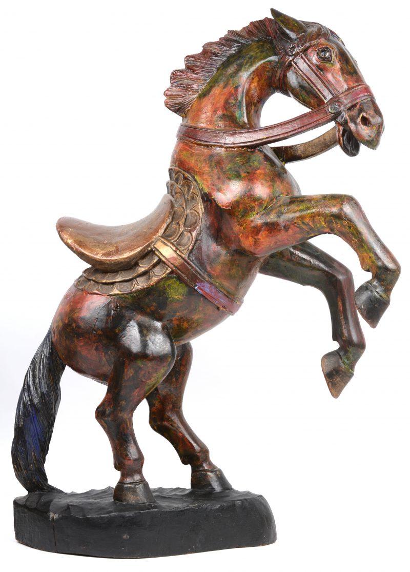 Een gebeeldhouwd en gepolychromeerd houten paard.