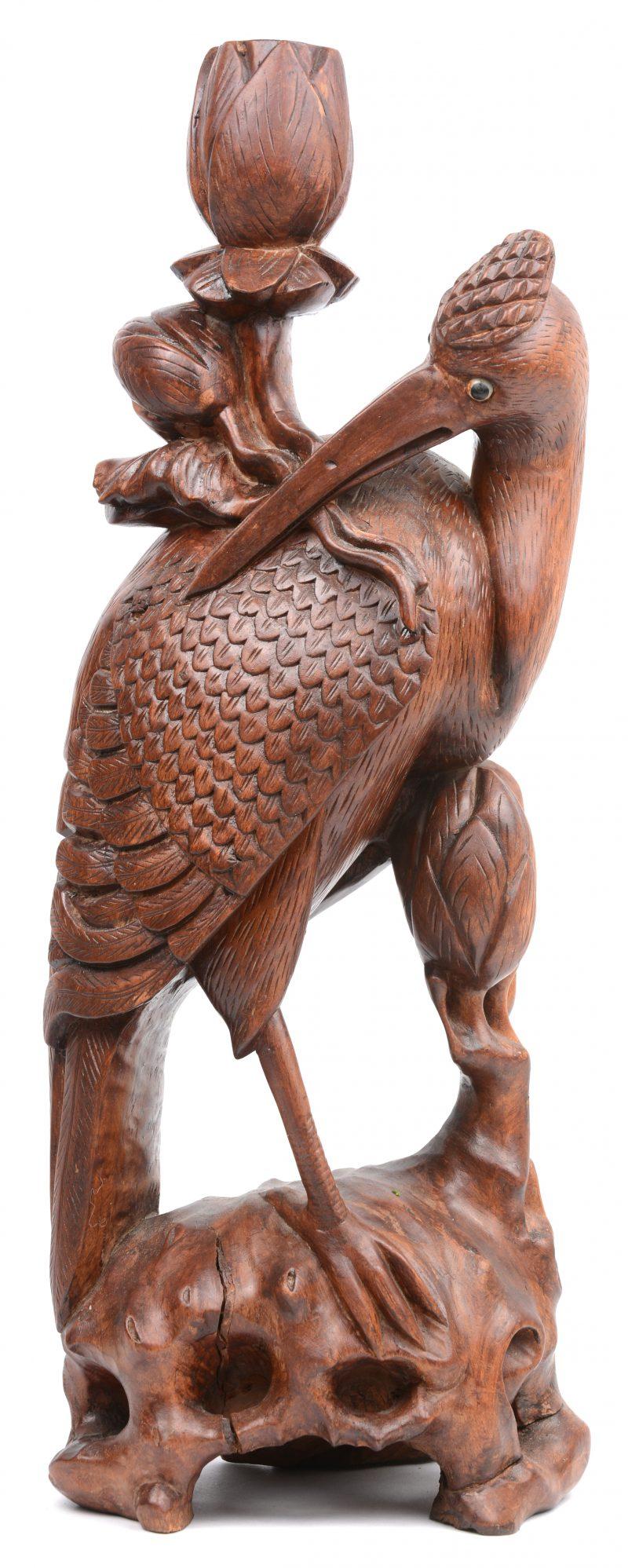 Een gebeeldhouwd houten lampvoet in de vorm van een kraanvogel.