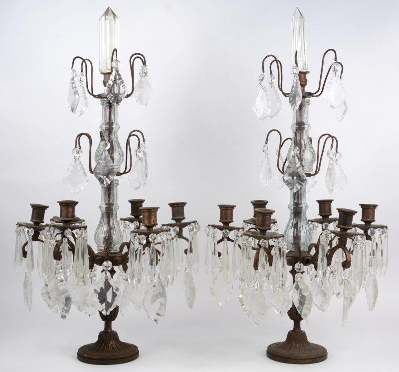 Een paar bronzen girandoles met zes lichtpunten en versierd met kleurloze kristallen pendeloques.