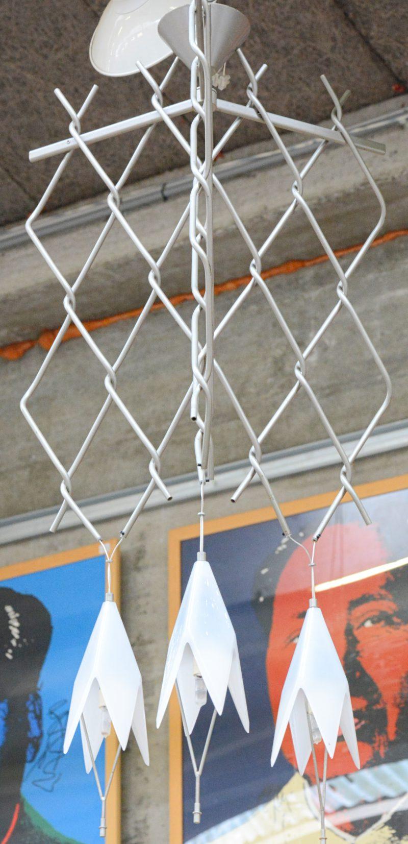 Een metalen designluchtertje met drie wit glazen kapjes.