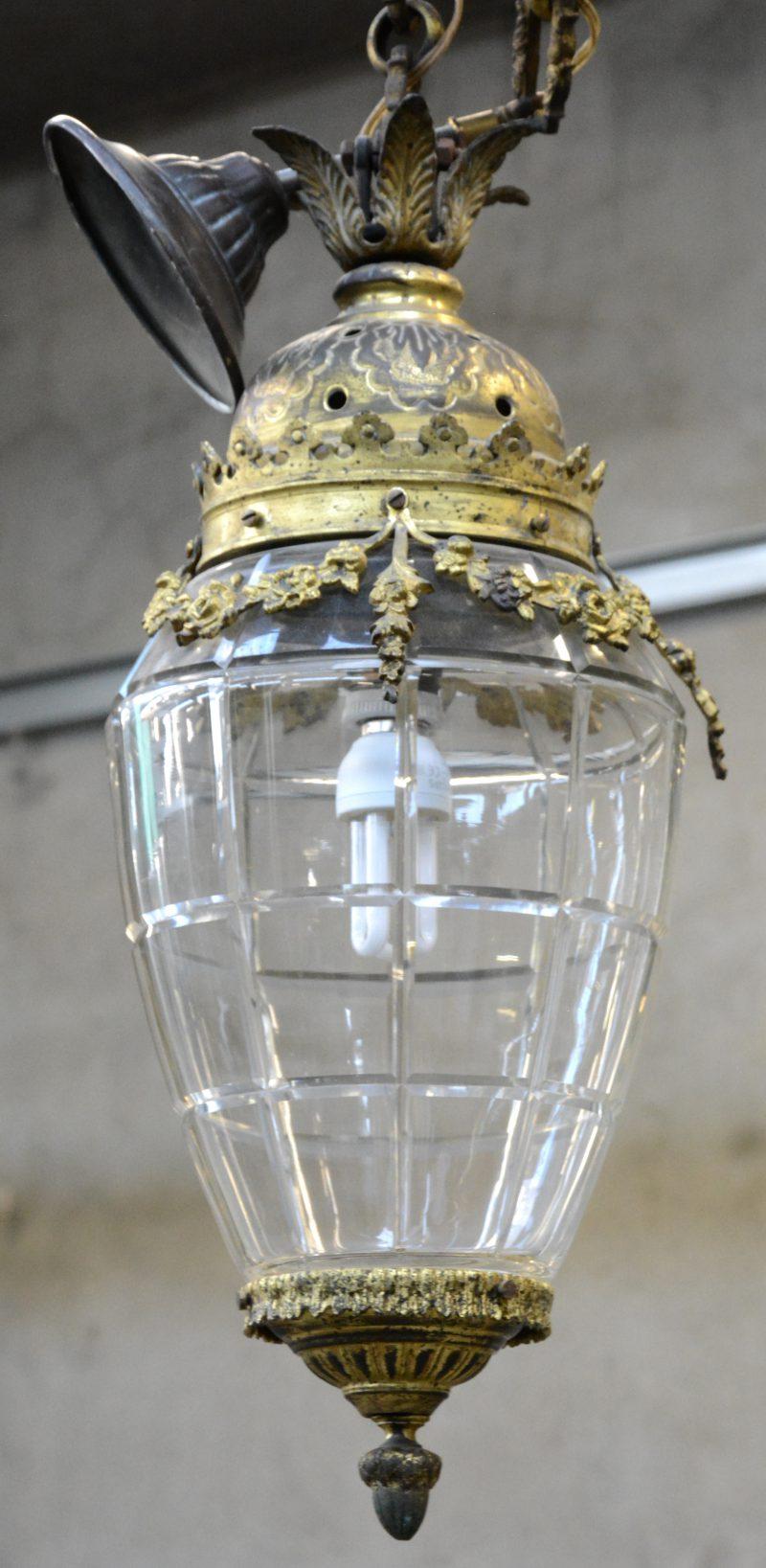 Een hanglantaarn van geslepen glas en verguld messing,  versierd met bladeren en bloemenguirlandes.