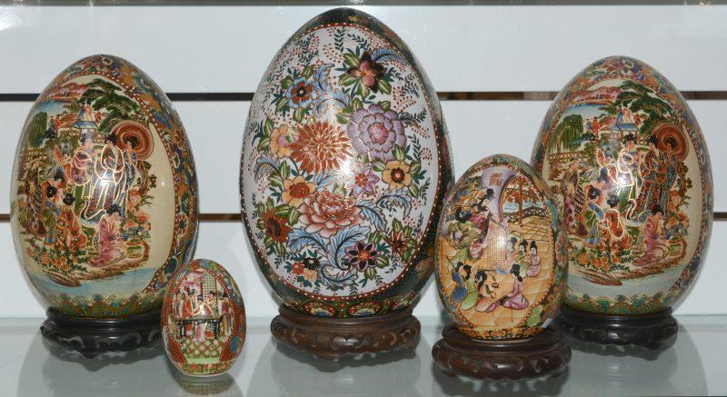Een lot van vijf eieren van Satsuma-aardewerk in verschillende groottes. Met houten sokkels.