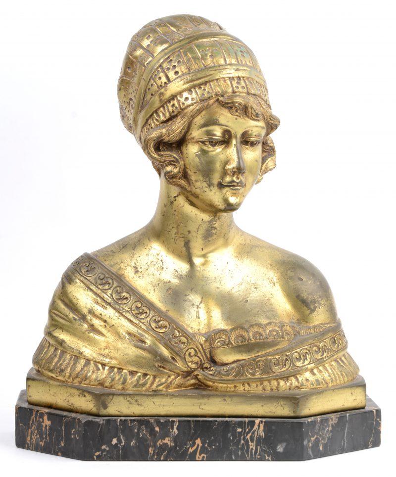 Een bronzen damesbuste zonder patina op zwart marmeren sokkel.