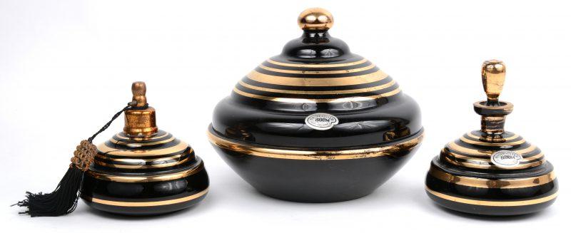 Een lot Booms glas met vergulde versieringen, bestaande uit een bonbonnière, een klein karafje en een parfumverstuiver. Alledrie gemerkt.