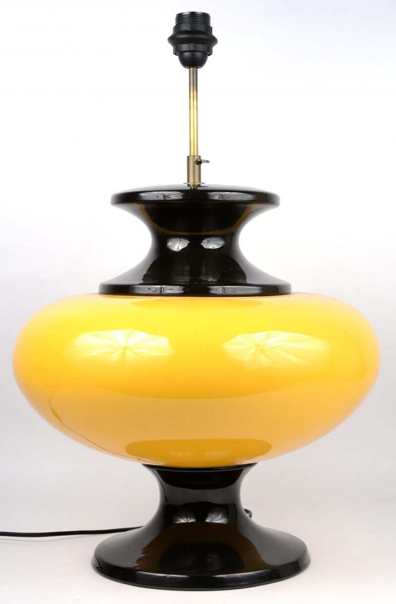 Een vintage lampvoet van geel en zwart glas.