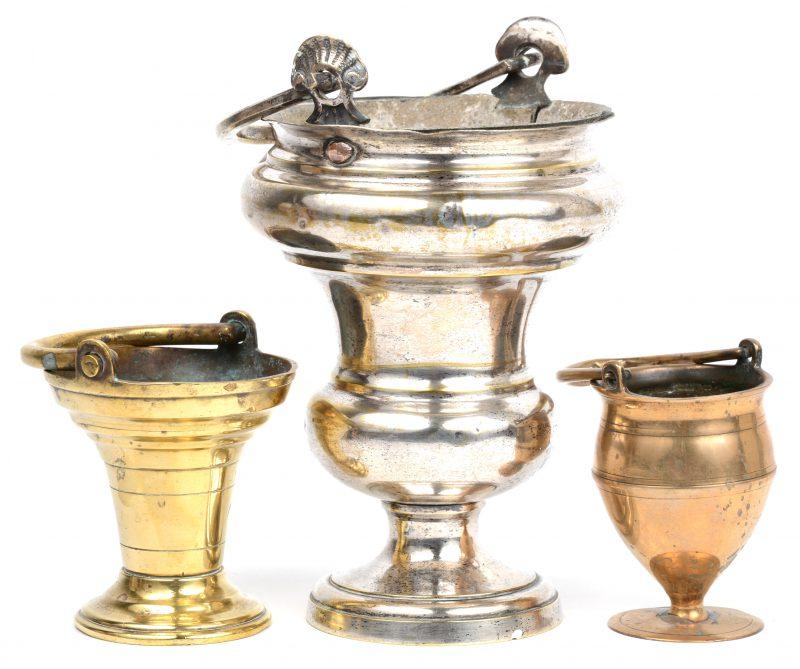 Een lot van drie wijwatervaatjes van brons en messing, waarbij één verzilverd. XVIIIe eeuw of ouder.