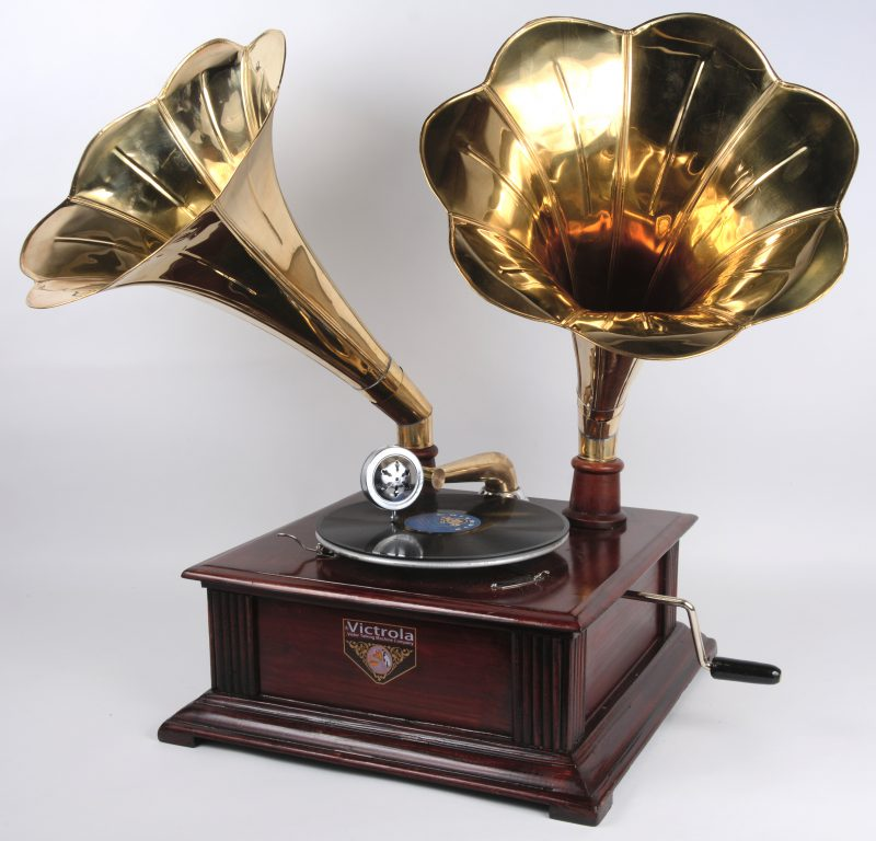 Een recente replica van een oude Victrola slingergrammofoon met dubbele messingen hoorn.