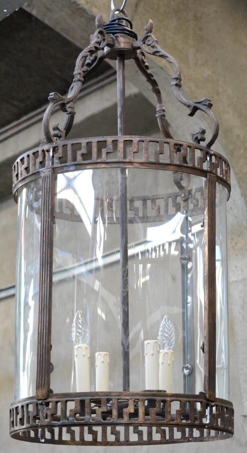 Een ronde bronzen hanglantaarn met bol glas.