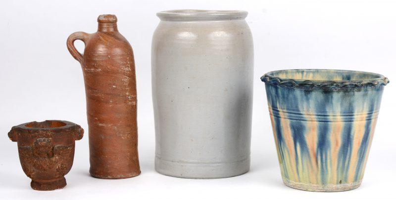 Een lot van vier stuks aardewerk en steengoed, bestaande uit een voorraadpot, een bloempot, een kruije en een klein potje.