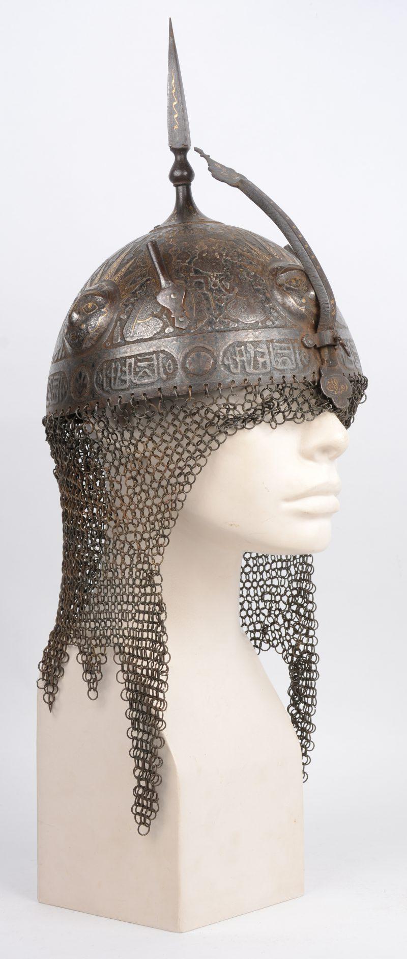 Een Perzische Kulah Khud helm met een gedamasceerd en geciseleerd decor op zwarte fond versierd. Boven op de bolle helm een vierhoekige punt en twee aigrettehouders en achteraan een maliënlap. XIXde eeuw.