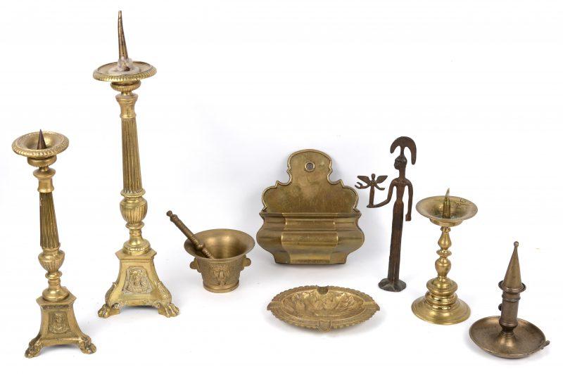 Een lot messing bestaande uit drie kandelaars, een vijzel met stamper, een asbak, een blaker, een wijwatervaatje en een beeldje.