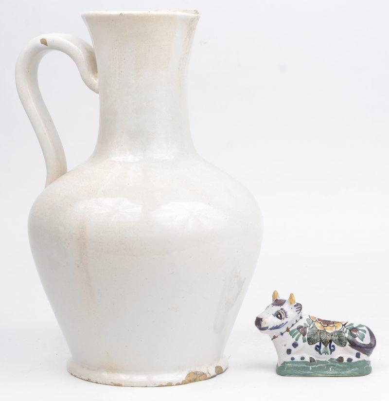 Een lot antiek Delfts aardewerk, bestaande uit een koetje en een schenkkan. De laatste gemerkt 'RK' onderaan.