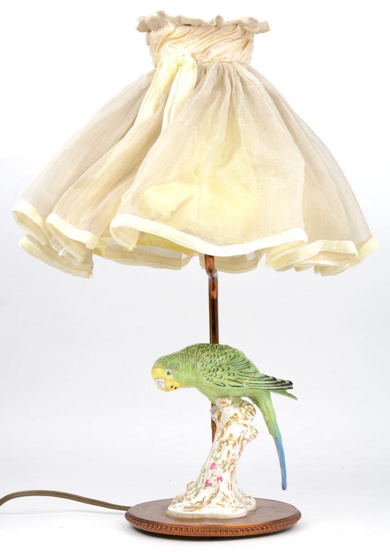 Een parkiet van meerkleurig en verguld porselein. Gemonteerd op een lampvoetje. Beschadiging aan een vleugeltje.