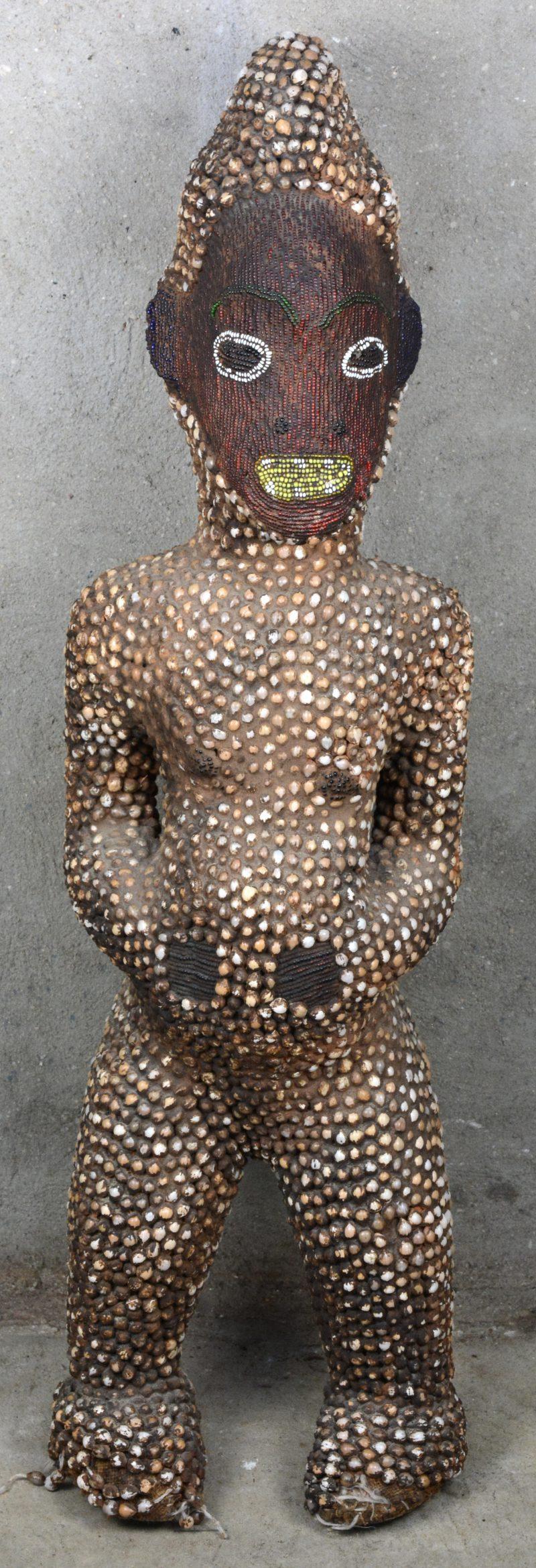Een Afrikaans houten beeld met kraaltjes/schelpjes.