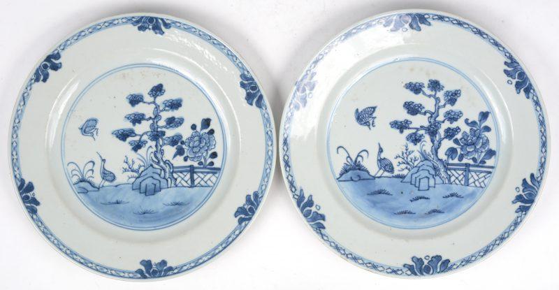 Een paar borden van Chinees porselein met een blauw op wit decor van een tuin. Tijdperk Qianlong.