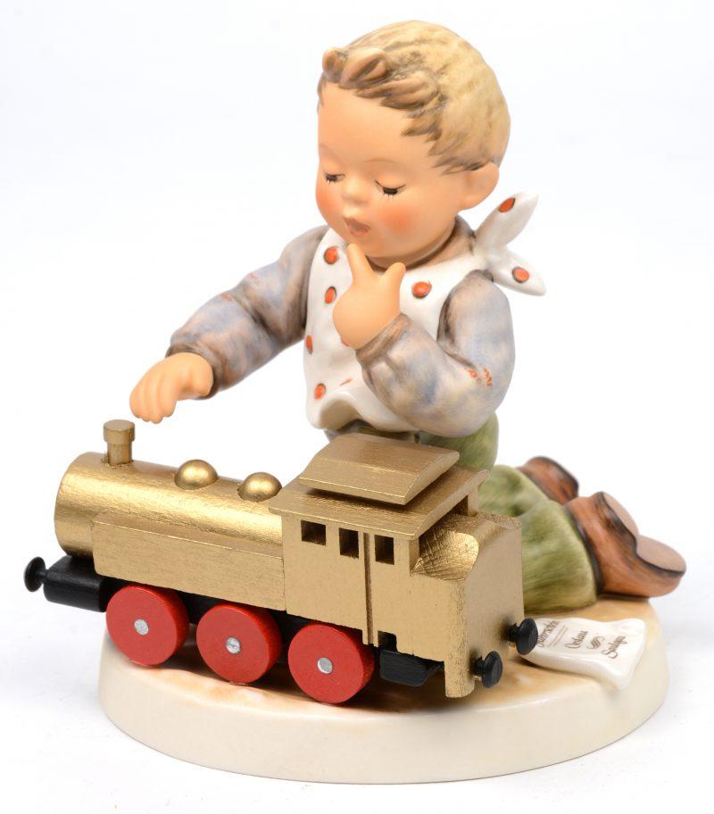 """""""Full speed ahead"""". Een groepje van meerkleurig biscuit met houten locomotiefje uit de reeks van M. I. Hummel. Onderaan gemerkt. Speciale uitgave No. 2157."""