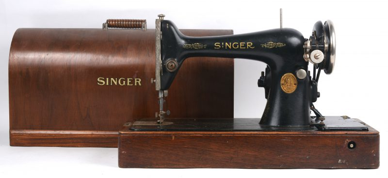 Een oude elektrische naaimachine in koffer.