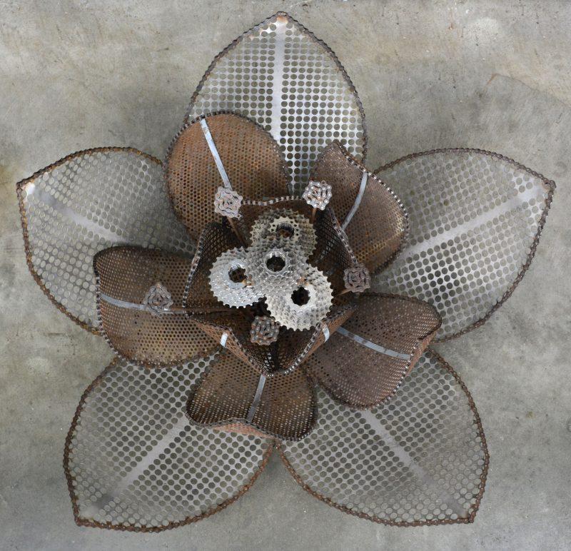 Een bloemvormige wand-/ plafondlamp, opgebouwd uit gerecycleerde materialen zoals tandwielen. Ontwerp van Laurence van Seventer.