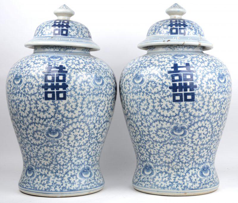 Een paar dekselvazen van Chinees porselein met Chinese tekens op een achtergrons van vegetale motieven.