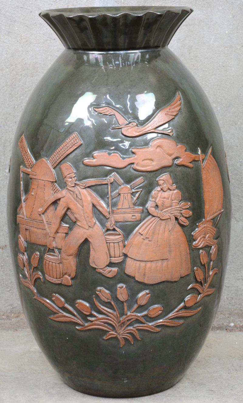 Een geëmailleerde terracotta vaas met een aziatisch en Hollands reliëfdecor. Onderaan gemerkt en gedateerd 10-2-1948.