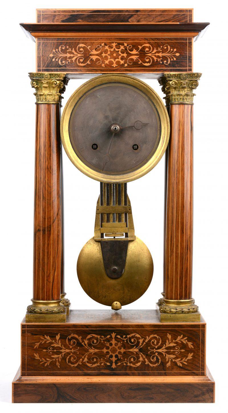 Een gefineerde kolompendule met verguld bronzen monturen. Met slinger, zonder sleutel.