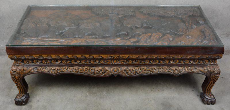 Een gebeeldhouwd hardhouten salontafel met een hoogreliëfdecor van olifanten in een landschap. Chinees werk.