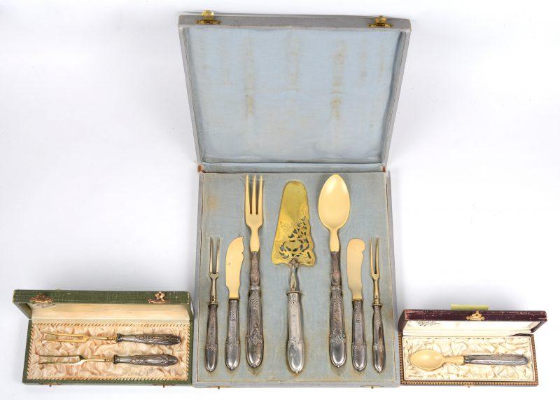 Een lot zilveren bestekken met zilveren handvatten, bestaande uit een etui met zevendelig serveerbestek, waarvan een slabestek met been, een etui met lepeltje met been en een etui met twee vleesvorken.
