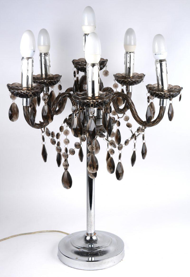 Een vijfarmige tafellamp met verchroomde voet en de lichtpunten versierd met geslepen rookbruin kristallen pendeloques.