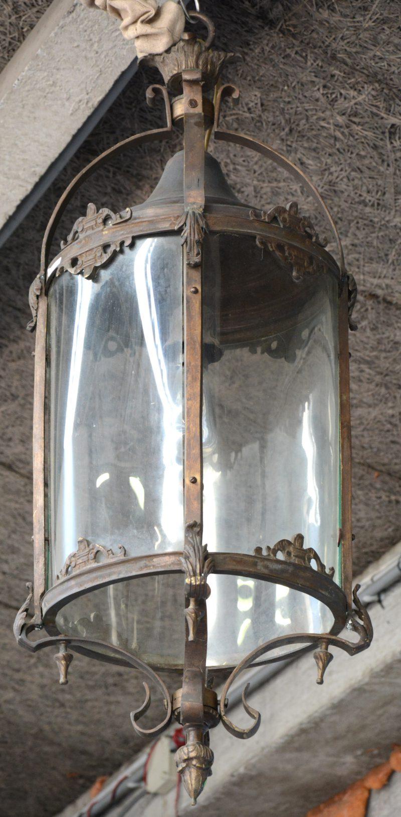 Een grote bronzen hanglantaarn met bol glas.