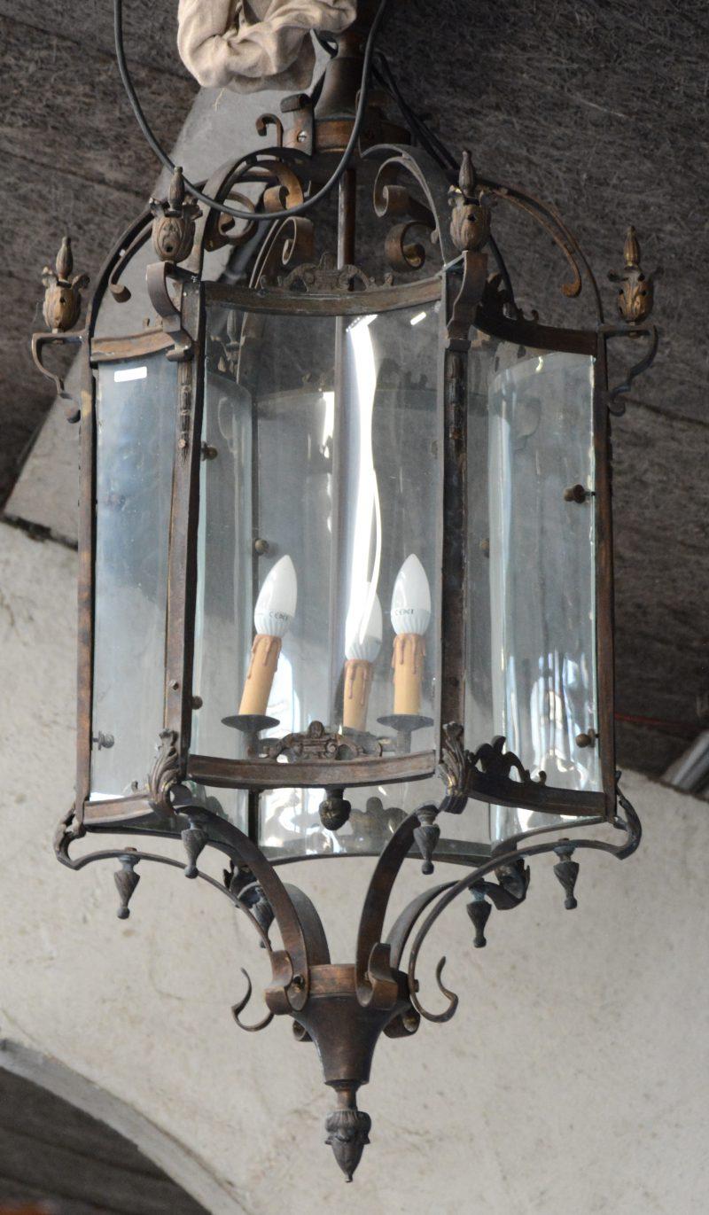 Een zeshoekige bronzen lantaarn met concave ruitjes.