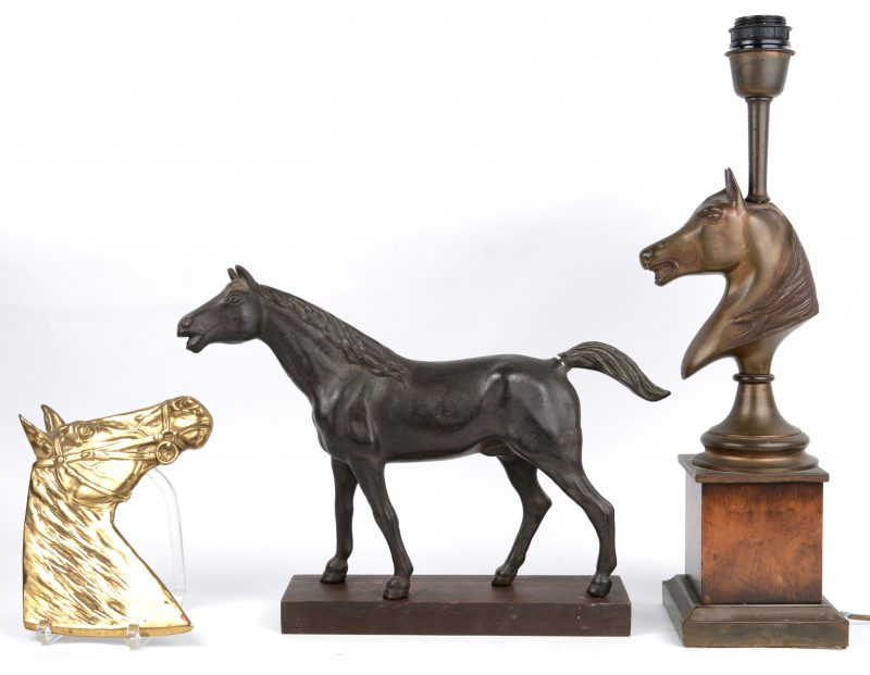 Een bronzen plaquette van een paardenhoofd een zamakken lampvoet met paardenhoofd en een hol bronzen paard met beschadigde staart.