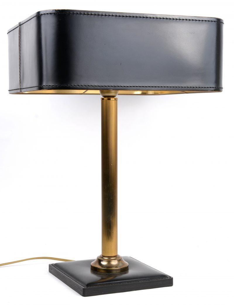 Een messingen bureaulamp met lederen voet en kap.