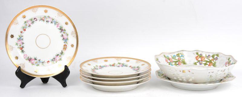 Een aardbeischaal met onderschotel van Beiers porselein, versierd met een opengewerkt en meerkleurig bloemendecor. Verguldsel vervaagd en een haarscheur. Onderaan gemerkt.We voegen er vijf borden met meerkleurig en verguld decor aan toe.