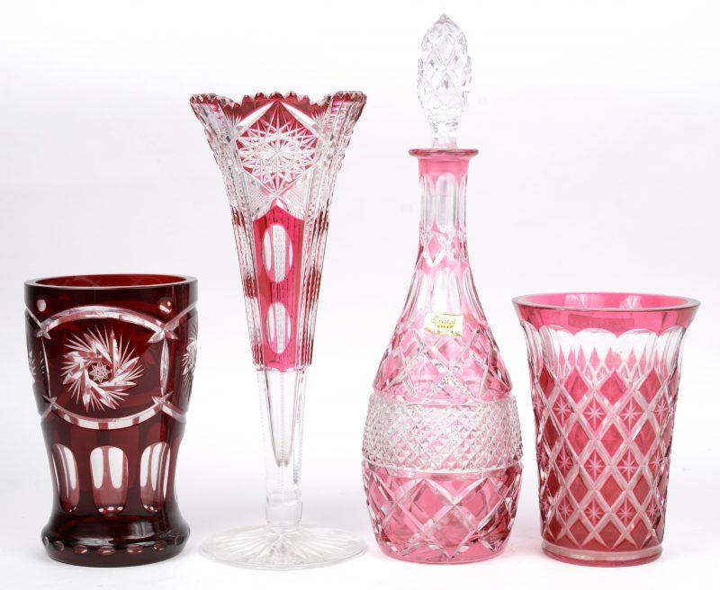 Een lot geslepen en gekleurd kristal, bestaande uit een karaf, twee vazen (één met randschilfer) en een fluitvaas op voet.