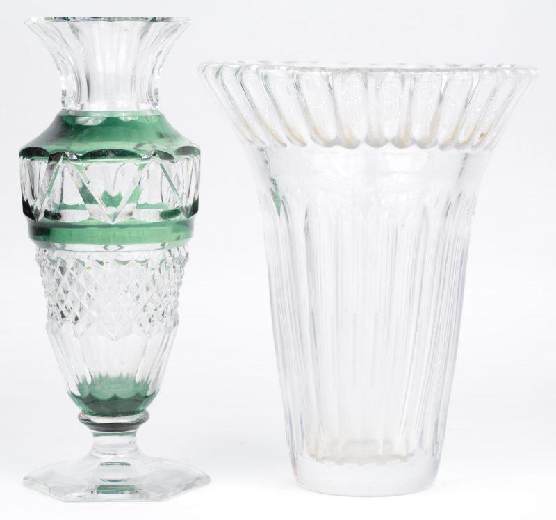 Twee vazen van geslepen kristal, waarbij één kleurloze en één groen gedubbeld. De tweede met schilfer onderaan de voet. Beide gemerkt.