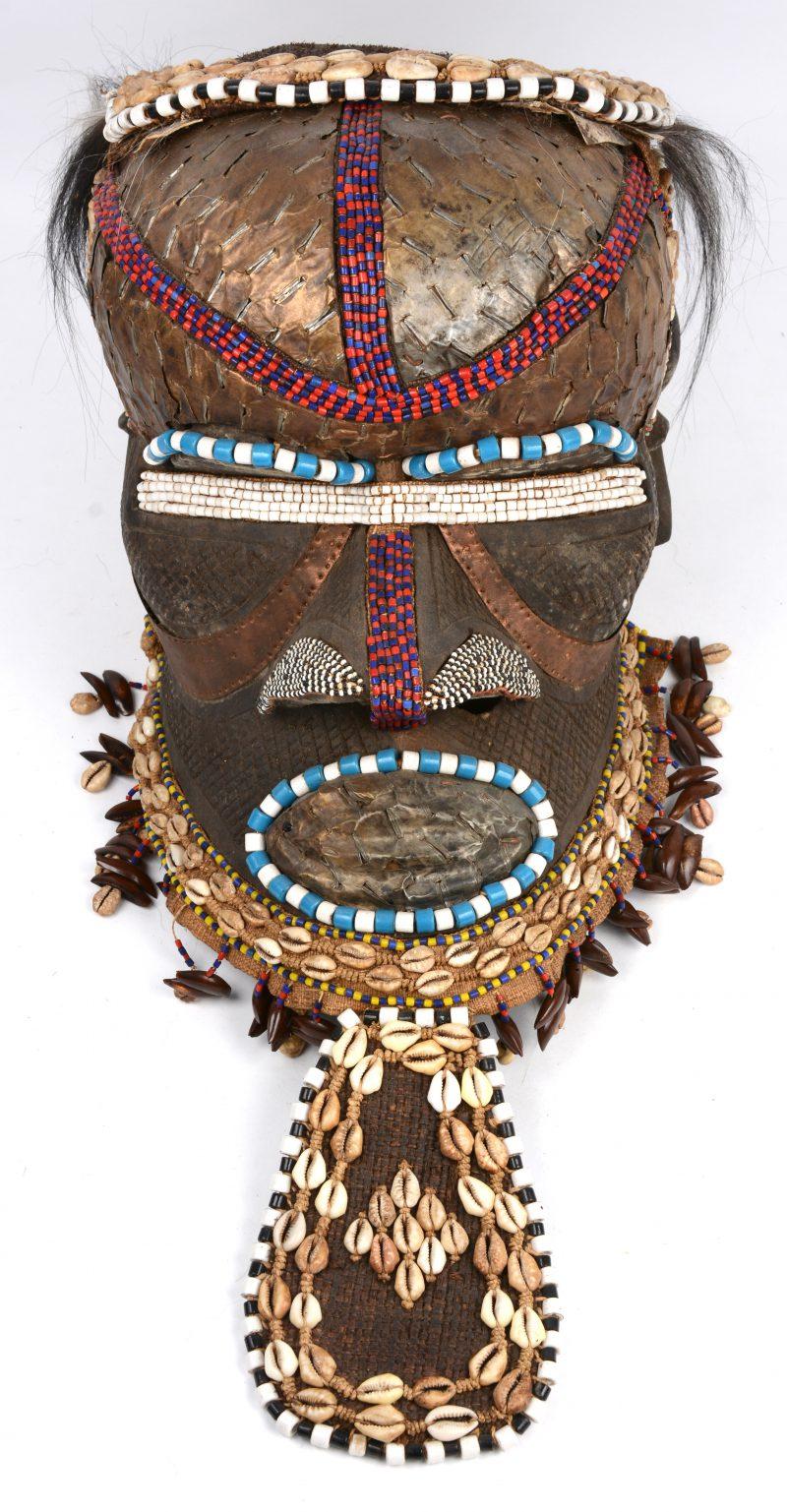 Kifwebe. Een Luba helmmasker, volledig bekleed met schelpen, koper, haar, kraaltjes enz. DRC.