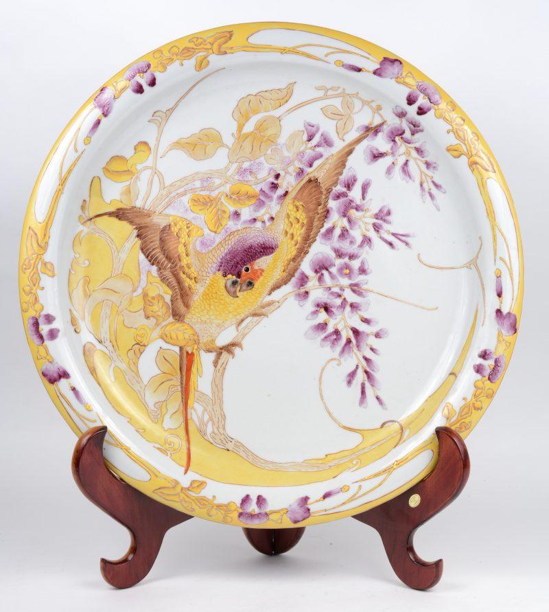 Een grote ronde sierschotel van porselein met een meerkleurig decor van een papegaai en bloemen. Onderaan gemerkt 'Rozenburg den Haag'.