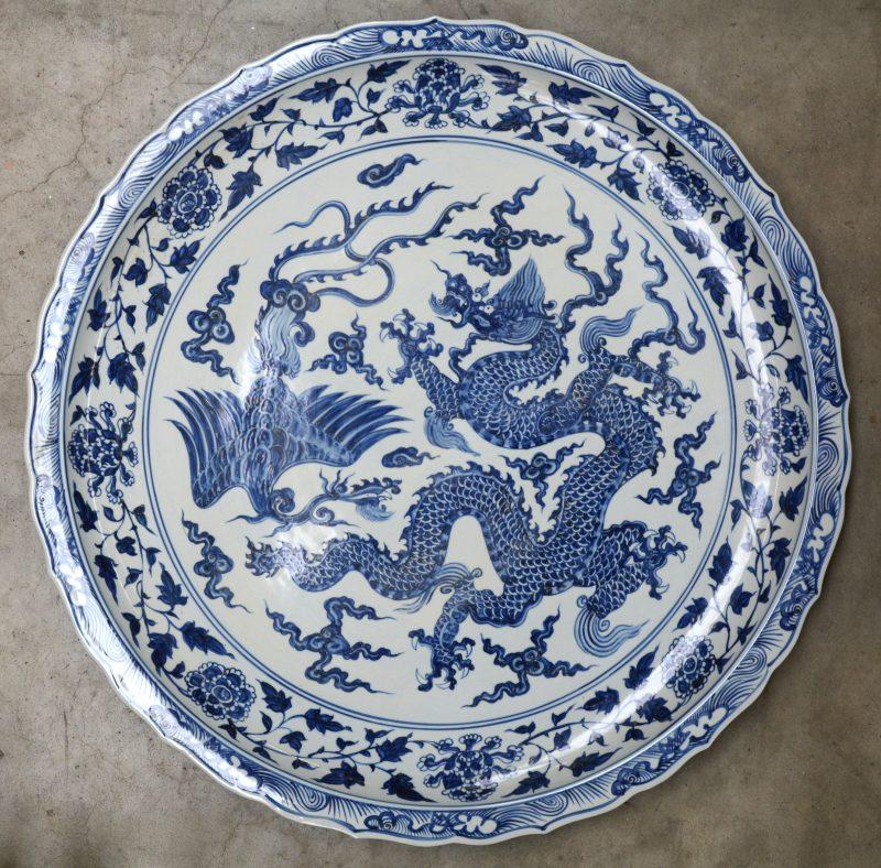 Een grote decoratieve schotel van Chinees porselein met een blauw op wit decor van een draak en een paradijsvogel.